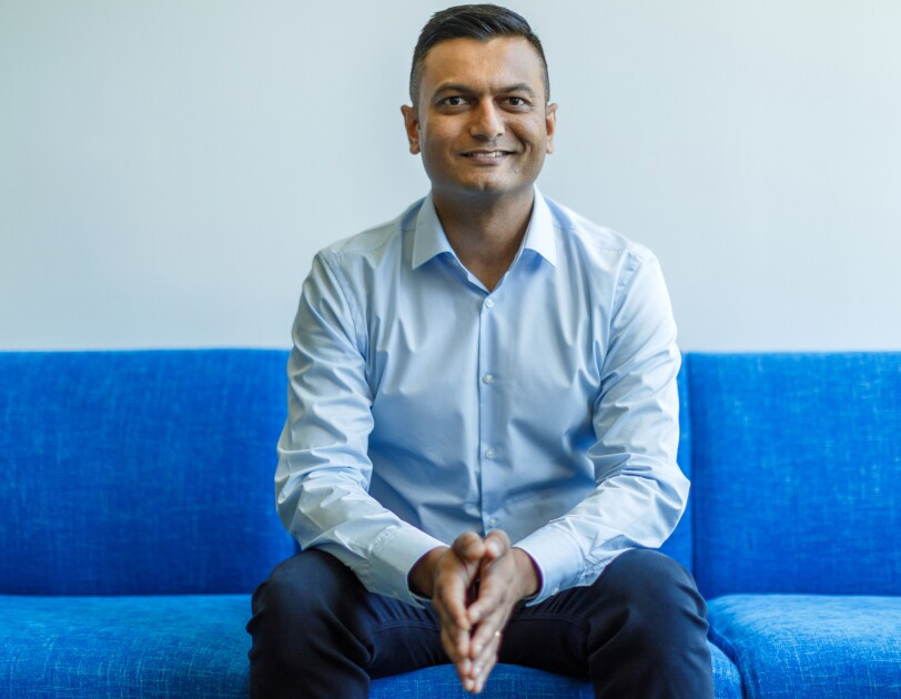 Amazon Music director of product management Kintan Brahmbhatt sits on a blue couch with his arms resting on his knees. He is wearing a blue shirt and jeans.