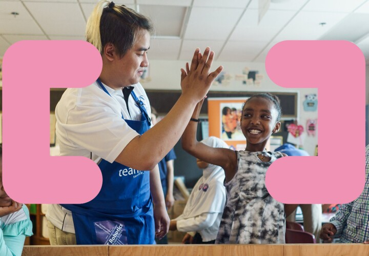 A teacher in a blue smock high fives a young student in a classroom setting. The image has two graphics of brackets overlaid.