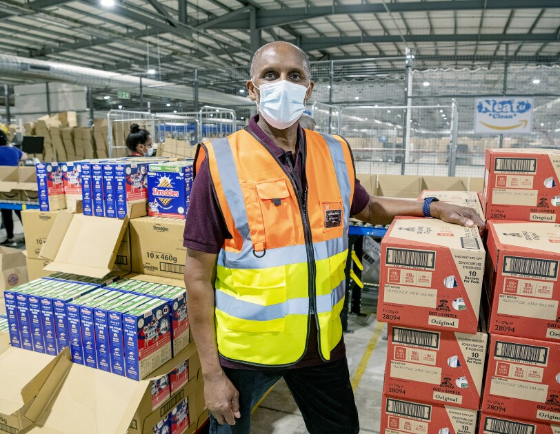 Amazon employee stands infront of food donations for Magic Breakfast