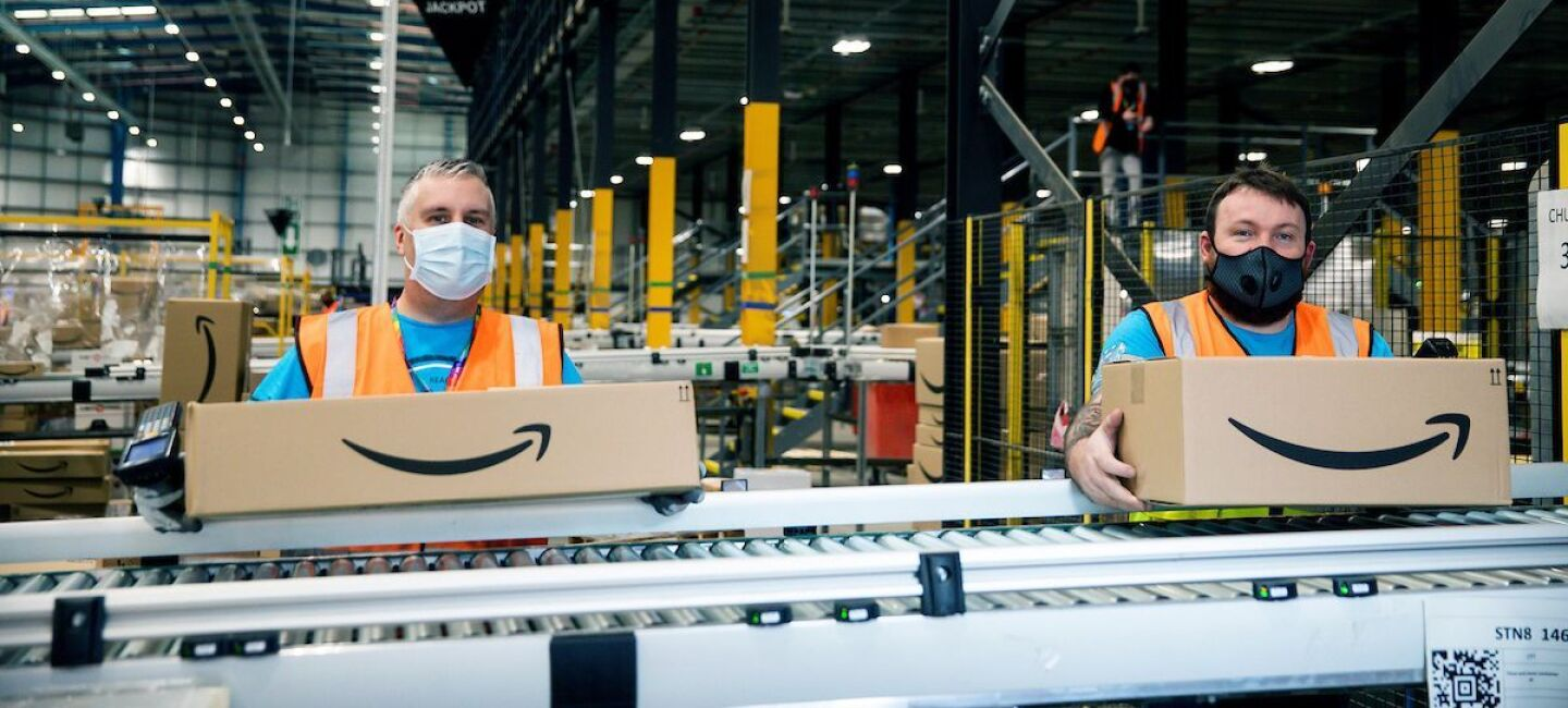 two men in masks with amazon boxes