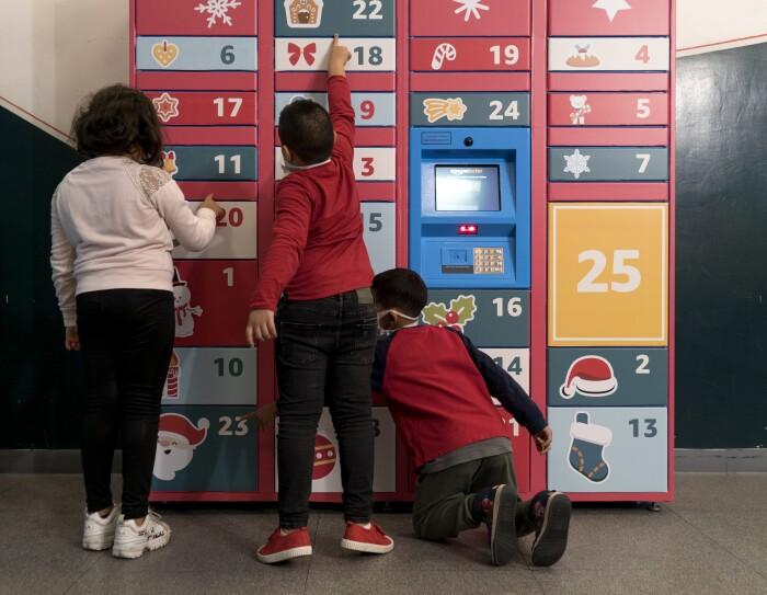 Locker Amazon ricoperto di adesivi natalizi su fondo rosso. Davanti ad esso giocano 3 bambini, ripresi di spalle.