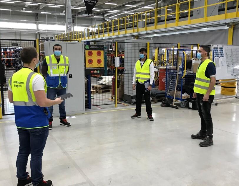 4 Mitarbeiter mit Sicherheitswesten und Masken in einer Logistikhalle