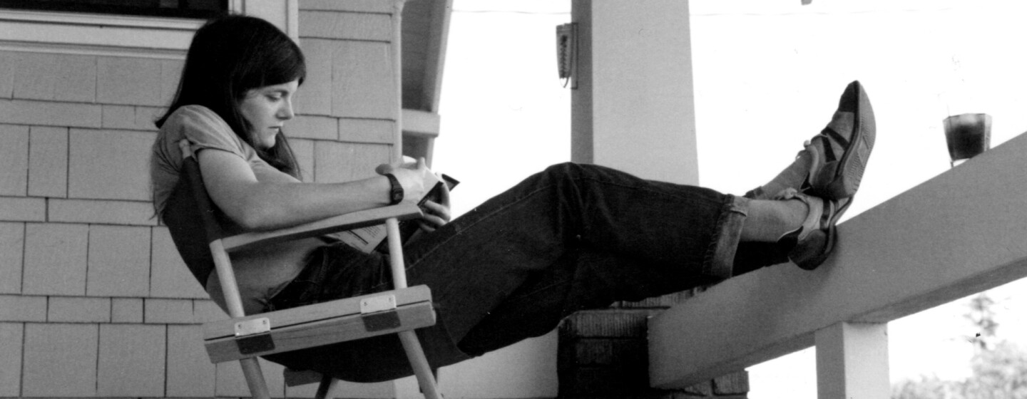 A vintage photo of a woman with dark hair, a tee shirt, jeans with a rolled cuff and tennis shoes, reading while sitting in a director's chair, her feet propped on the ledge of a craftsman-style home's porch.