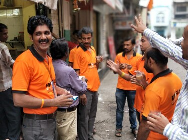 Amazon employees in orange shirts communicate with each other in sign language on a street in Mumbai, India.