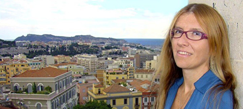 Ritratto di Carla Monticelli, una delle 10 autrici indipendenti italiane più apprezzate. La donna si trova sulla destra dell'immagine, mentre sullo sfondo si vede un panorama della città di Cagliari.