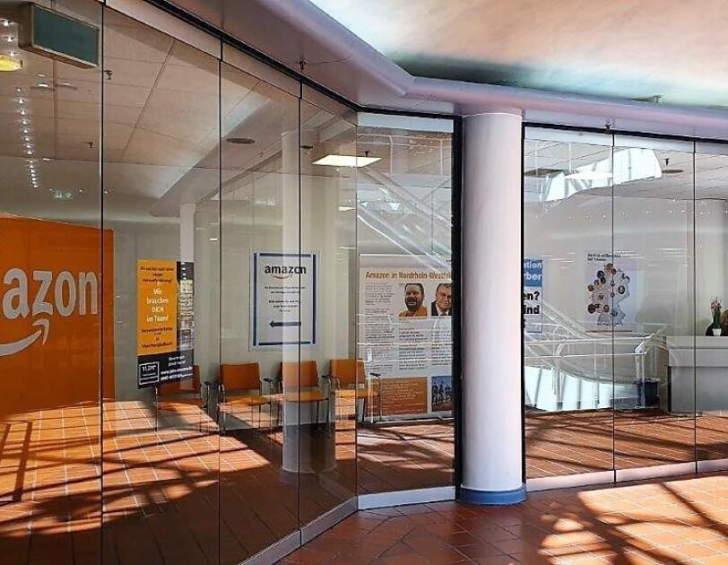 Ein mit Glas eingefasstes Bürogebäude von außen: Man sieht Amazon Poster und Logos sowie die  weiße Empfangstheke