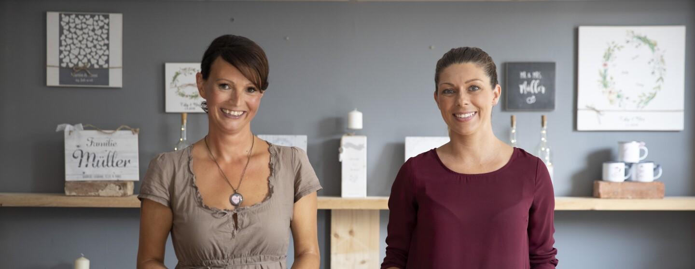 Yivi und Anja von Manufaktur Liebevoll stehen in ihrem Laden und lächeln in die Kamera.