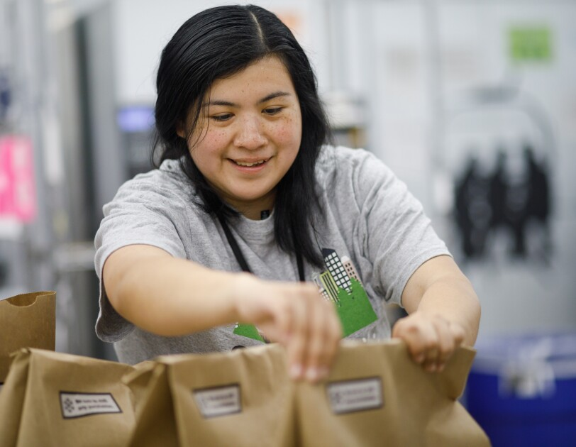 Prime Now associate Erika Lopez arranges brown paper shopping bags.