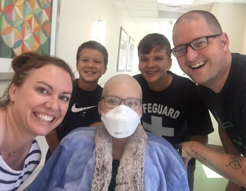 A woman, two boys, and a man pose with a girl wearing a hospital mask and glasses.