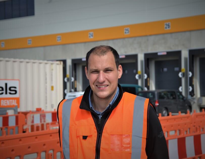 Ein Mann mit braunen kurzen Haaren und orangener Sicherheitsweste vor neinem Logistikzentrum. Man sieht Absperrungen und die Laderampen.