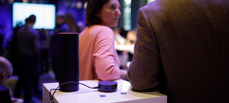 Ein Amazon Echo steht auf dem Tisch. Darum stehen Menschen, die sich unterhalten.