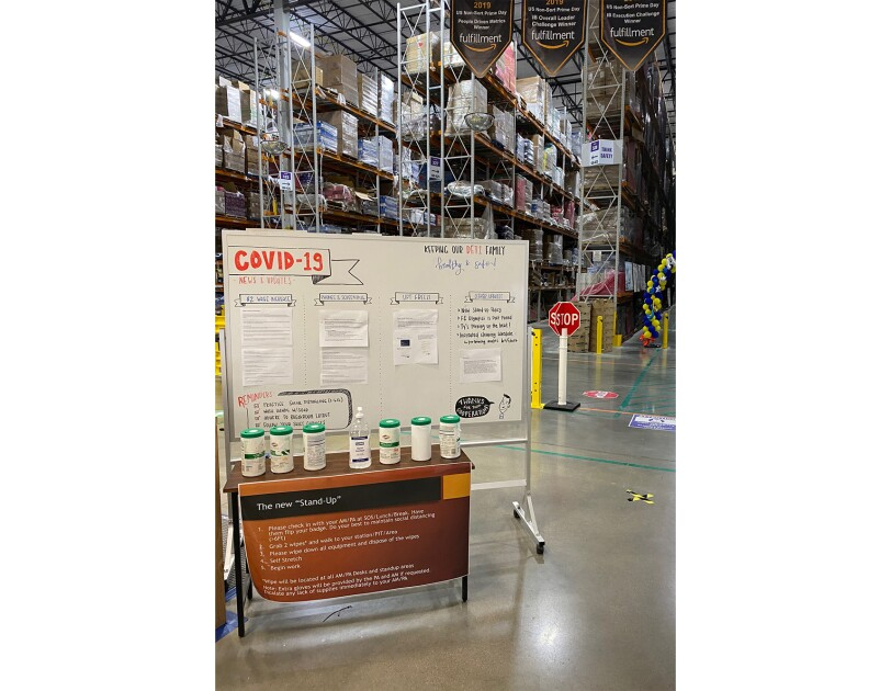 A white board inside an Amazon fulfillment center with information about work, and a table with antibacterial supplies for associates to use.