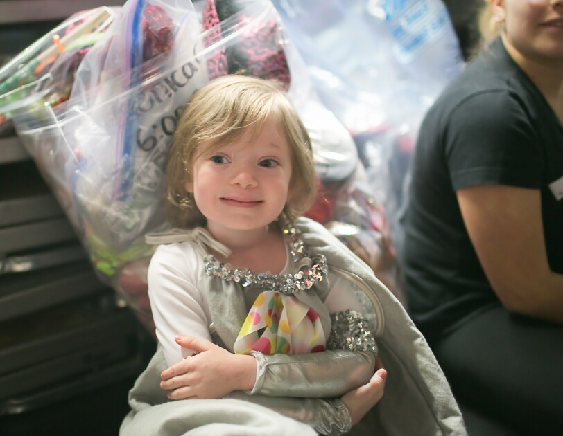A young girl with short hair wearing a costume backstage at a dance performance.