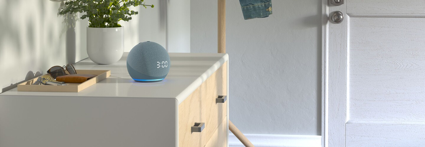 An image of an Alexa-enabled device sitting on a table in the entryway of a home.