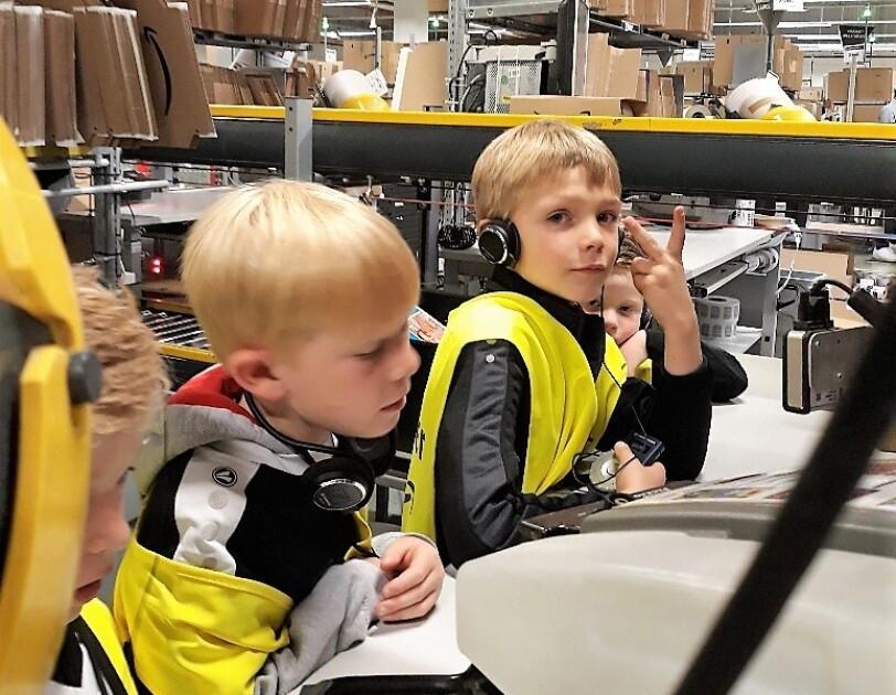 Zwei kleine Jungs in gelben Sicherheitswesten an einem Packtisch: Einer macht das Siegeszeichen