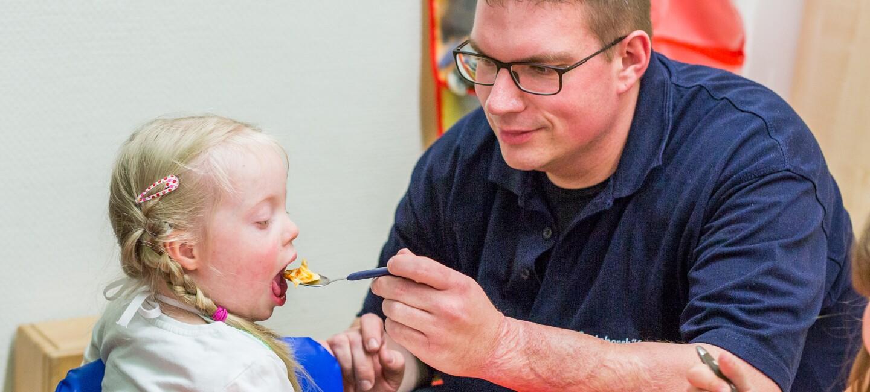 Der Vater füttert seine erkrankte Tochter mit einem Löffel. Beiden sitzen am Kindertisch.
