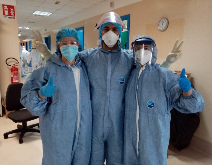 Tre persone in un ospedale indossano tute protettive e dispositivi di protezione personale come mascherine e guanti. Guardano verso la fotocamera e salutano.
