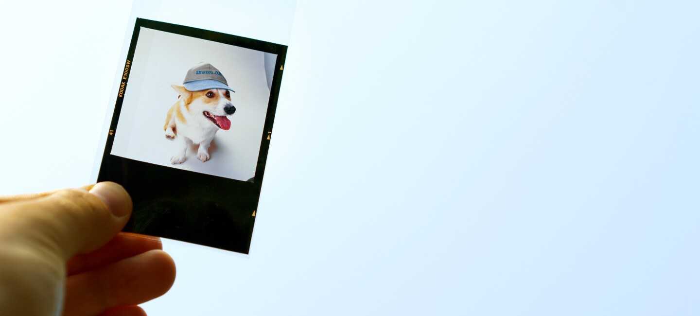 A hand holds a photo negative that contains a picture of a Welsh Corgi named Rufus, the first dog of Amazon. He is wearing a hat that says amazon.com.