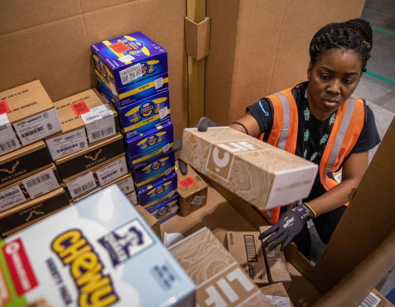 A woman in a safety vest loads packaged foods into a large box.