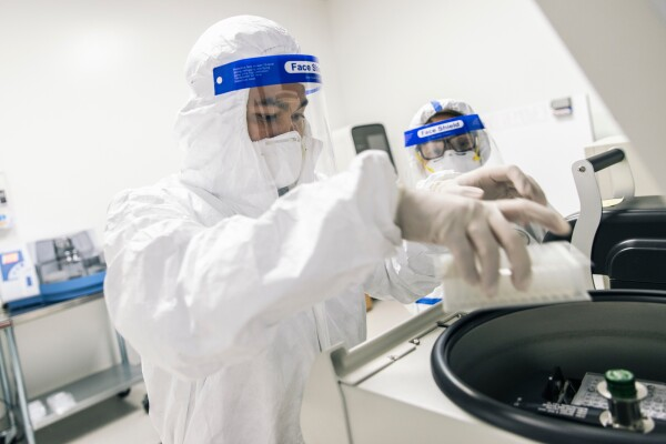 Two people wearing PPE work in a lab. The person in the foreground places a tray in lab equipment.