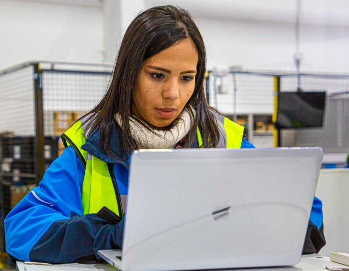 Ivette Duran, CEO de Canaima Logistics, trabajando en un centro logístico de Amazon. Está sentada en una mesa trabajando con un ordenador. Tiene el pelo largo de color negro y es morena de piel. Lleva un jersey de color blanco y encima una chaqueta azul con el logo de Prime Now y un chaleco fluorescente.