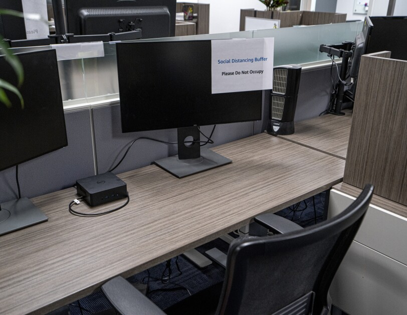 "An office area where a computer monitor has a sign taped to it that says ""Social Distancing Buffer"" and ""Please Do Not Occupy."""