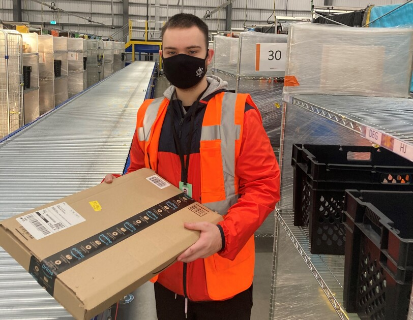 Finlay Shouler, Sortation Associate at Amazon's delivery station in Sheffield , pictured holding an Amazon parcel next to a conveyor belt.