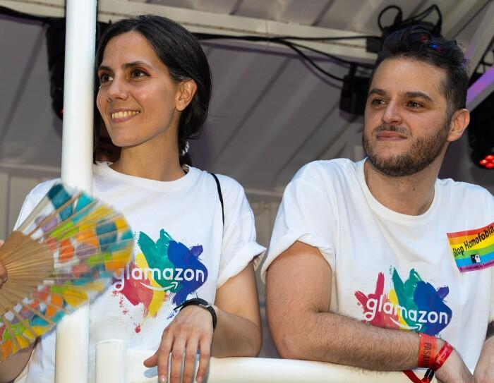 Eva y Simone en la carroza del desfile del Día internacional del orgullo LGTBI en Madrid. Los dos lucen la camiseta de glamazon y están apoyados en la barandilla de la carroza. Miran hacia su derecha con una sonrisa. De fondo se ve la carroza blanca y un foco de color rojo.