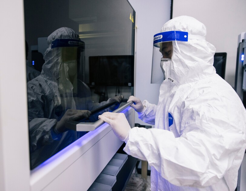 A person in PPE closes a piece of lab equipment.
