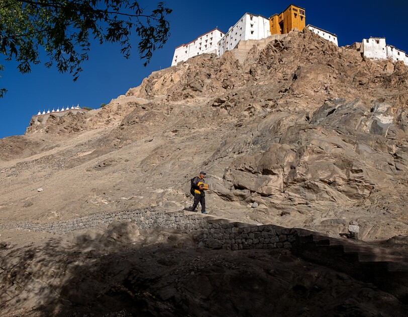 A person carrying a cardboard package walks along a stairway set into a rocky hillside. High above in the background white buildings are on a hilltop.