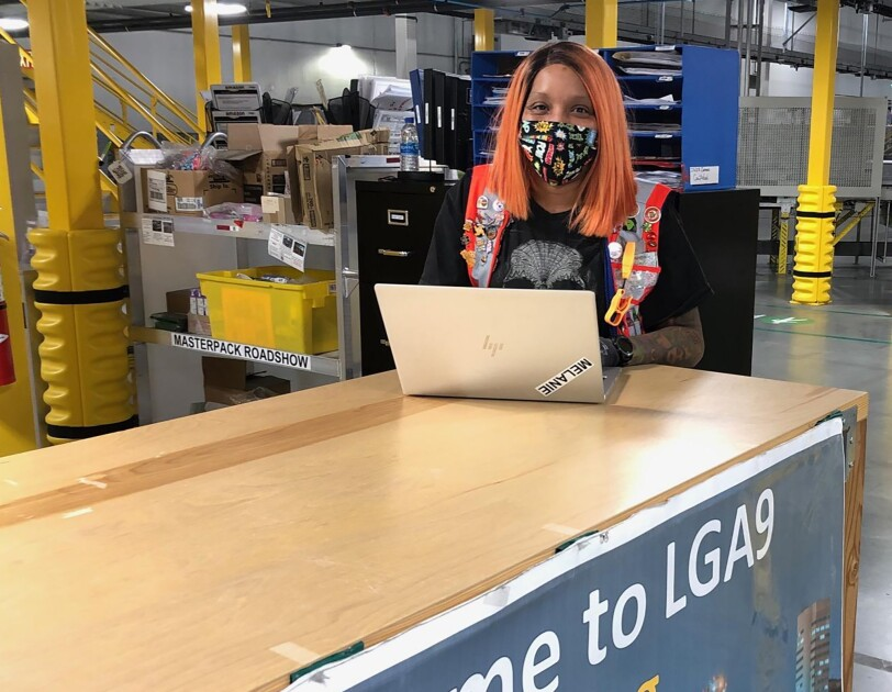 Woman Amazon associate wearing a mask while working