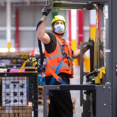 Dipendente di un magazzino Amazon. Indossa un casco, una mascherina chirurgica e un giubbino di sicurezza, si trova al centro di un macchinario. Alle sue spalle un cesto con dei pacchi Amazon.