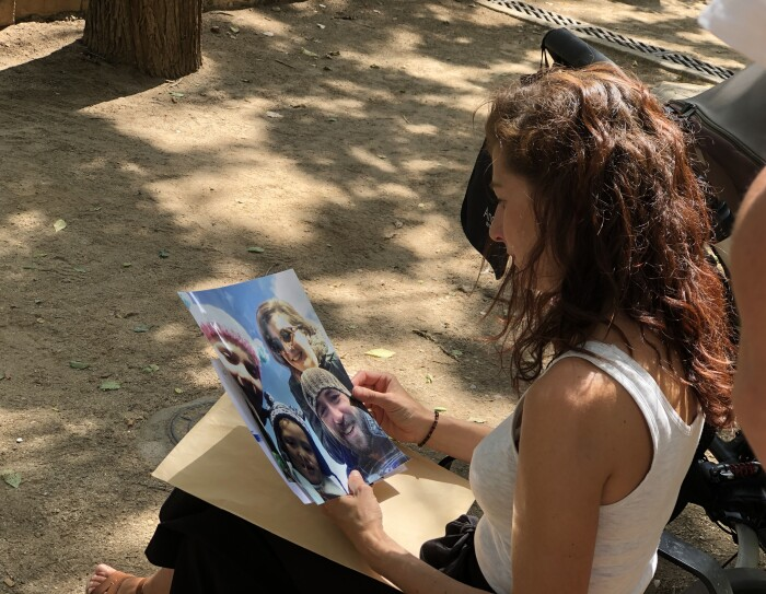 Irene sentada en un banco de un parque observa una fotografía de su familia. La sujeta con las dos manos. Viste con un jersei blanco sin mangas y una falda negra larga hasta los pies.