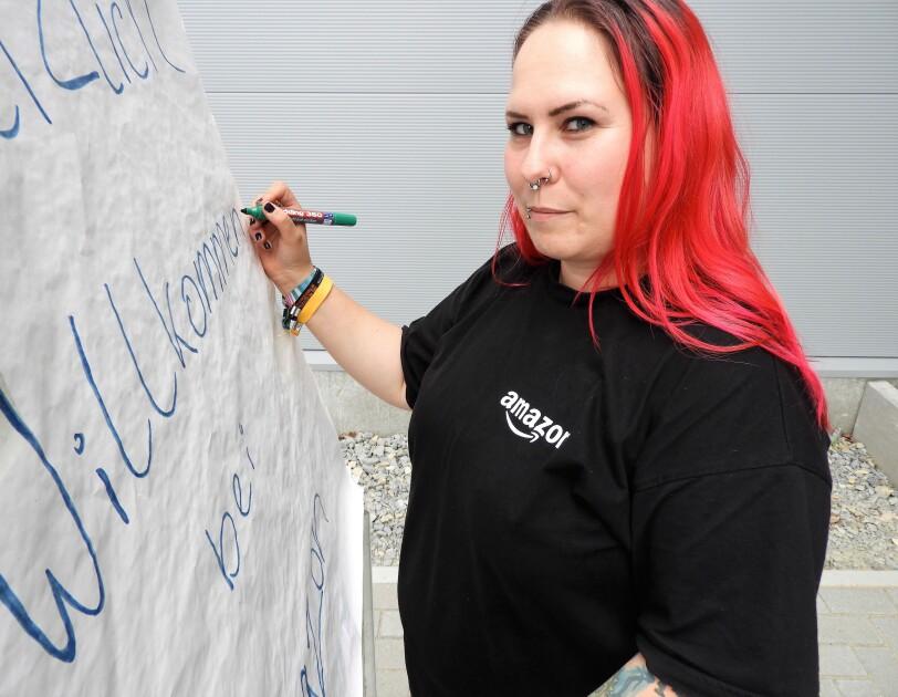 """Eine rothaarige Frau mit langen Haaren und schwarzem T-Shirt mit der Aufschrift """"Amazon""""  schreibt auf ein Flip-Chart """"HERZLICH WILLKOMMEN"""": Das ist Bentje."""