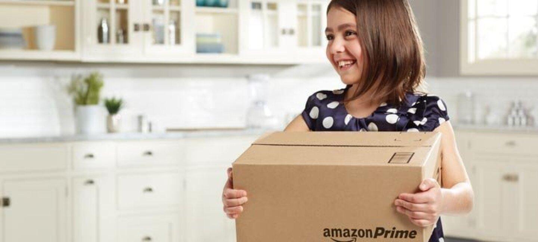 Niña de unos ocho años en la cocina de su casa, vistiendo un jersey de lunares, agarra con sus dos manos una caja con el logo de Amazon Prime.