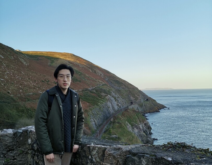 Fangbo Li standing in front of a coastal view