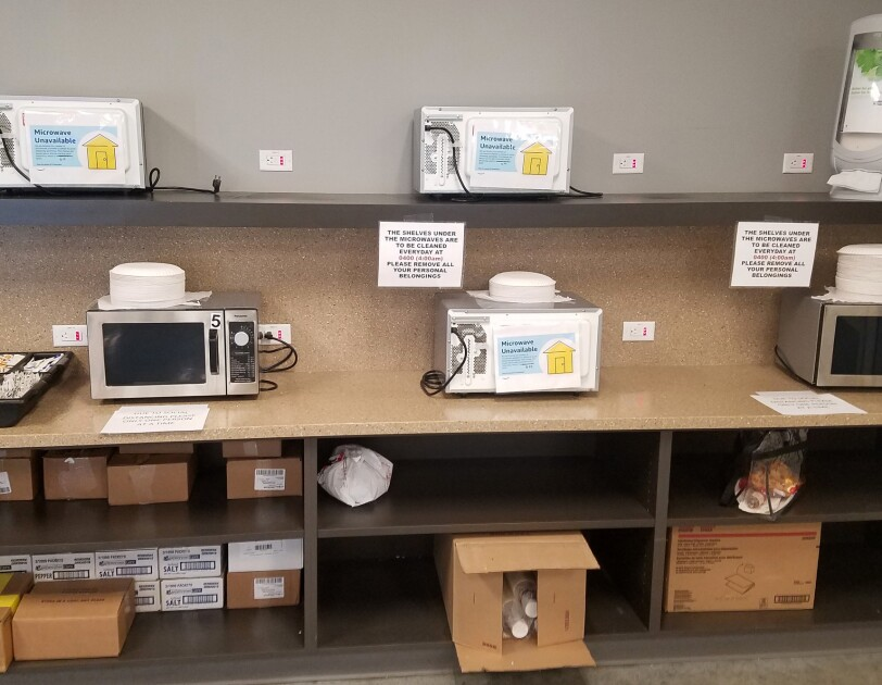 "Five microwave ovens on counters. Three are covered with signs saying ""Microwave Unavailable."""