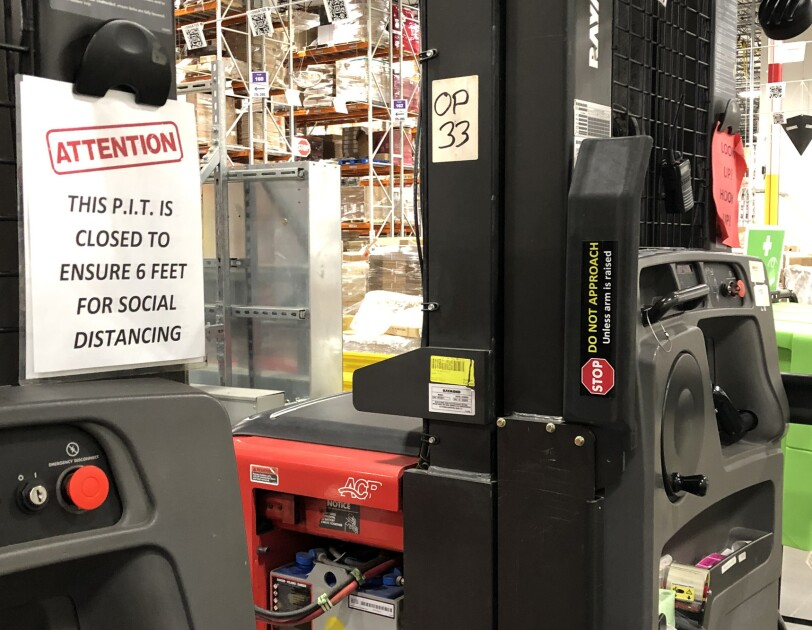 "View inside an Amazon fulfillment center with a sign that says ""Attention: this P.I.T. is closed to ensure 6 feet for social distancing."""