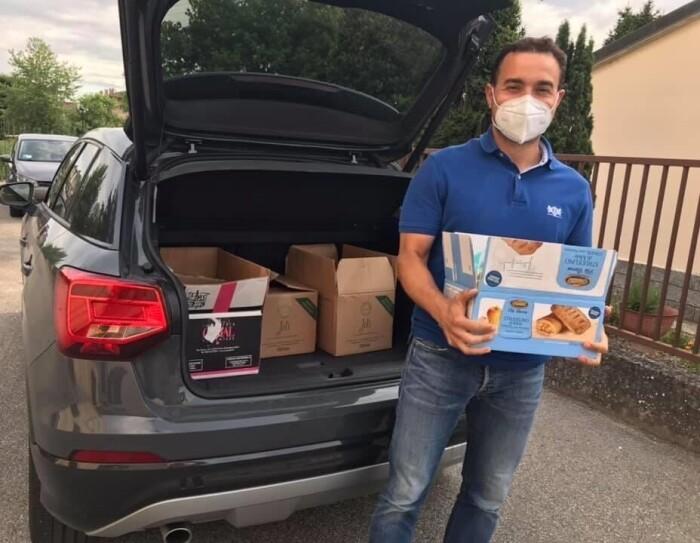 Un uomo davanti al baule di un'auto pieno di pacchi e viveri. Indossa una mascherina sul volto e regge con le mani un pacco di viveri.