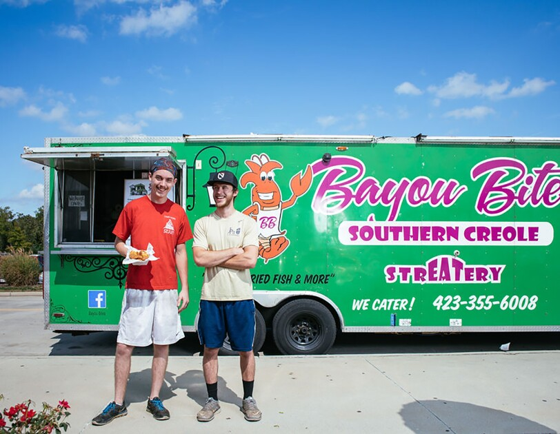 "Two men stand together in front of a green food truck branded with ""Bayou Bites - southern creole."" The man on the left holds a basket of food, and wears a headscarf, t-shirt, basketball shorts and athletic shoes. The other man wears a baseball cap, t-shirt, basketball shorts and athletic shoes."