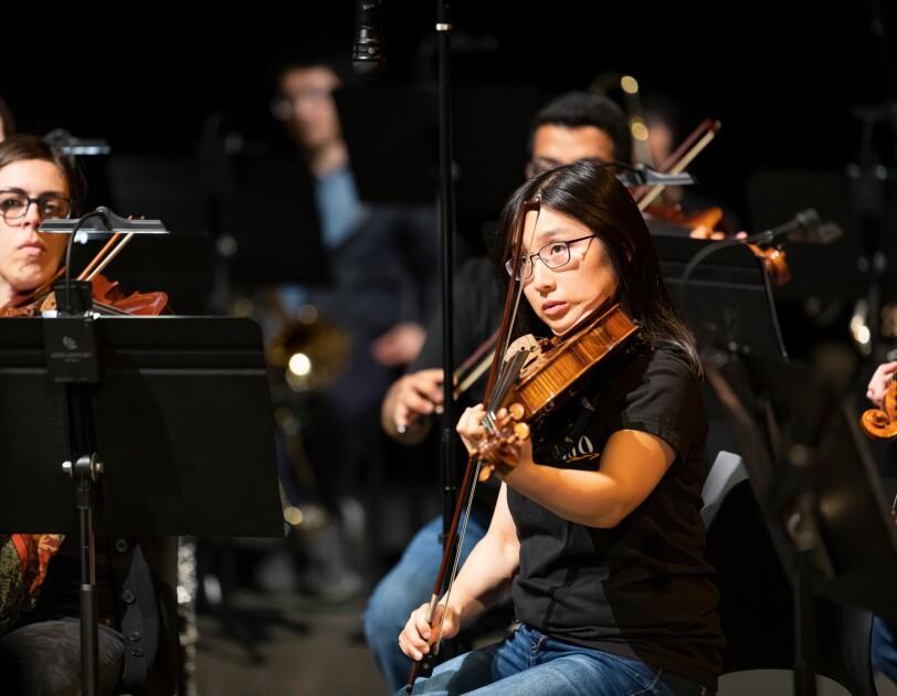 Członkowie orkiestry symfonicznej Amazon. Z przodu kobieta grająca na altówce, po lewej kobieta grająca na skrzypcach, w tle pozostali członkowie orkiestry.