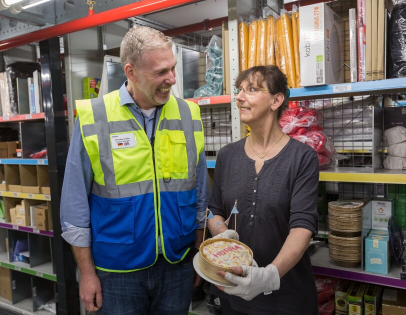"""Der Standortleiter übergibt  einer Mitarbeiterin eine kleine Torte, auf der in roten Zuckerbuchstaben """"HURRA"""" zu lesen ist. Im Hintergrund sieht man ein Regal, in dem viele Produkte gelagert werden."""