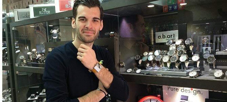 Aurélien Cram se tient devant une vitrine remplie de montres et arbore une montre à son poignet
