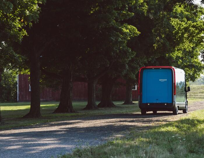Retro del furgone elettrico Rivian, ripreso su una strada di campagna con una fila di alberi sullo sfondo. Il baule sul retro è azzurro con il logo Amazon in alto a destra