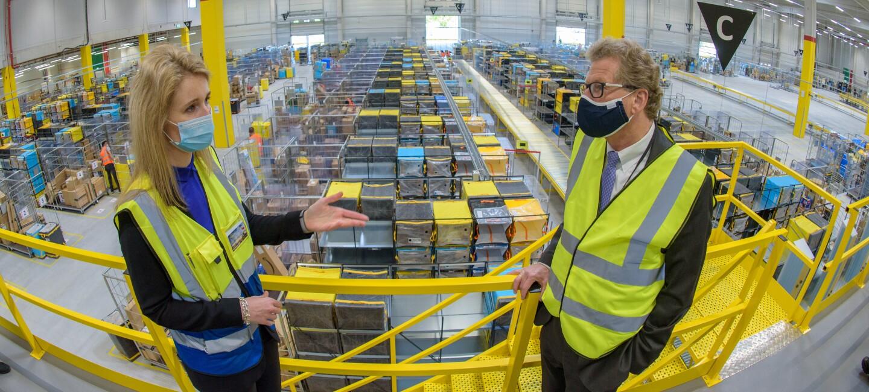 Der Minister steht rechts zu einer Amazon Managerin