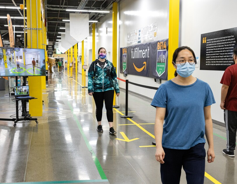 Amazon associates wearing face masks walk along a corridor of a fulfillment center. Behind them, a screen shows visual social distance assistance.