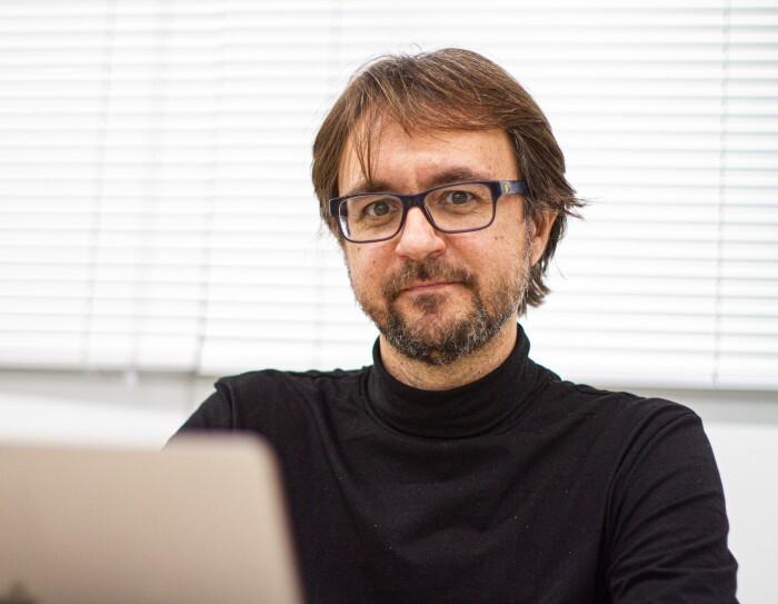 Hugo Zaragoza, investigador del Amazon Search Science y AI Group. Está en la oficina con unas cortinas detrás y un ordenador. Todo es de color blanco. ´Él lleva un jersey de cuello alto y unas gafas negras. Tiene barba y perilla de una semana y el pelo por las orejas. Estña mirando a cámara. Tiene barba negra con pelos blancos, y el pelo castaño.