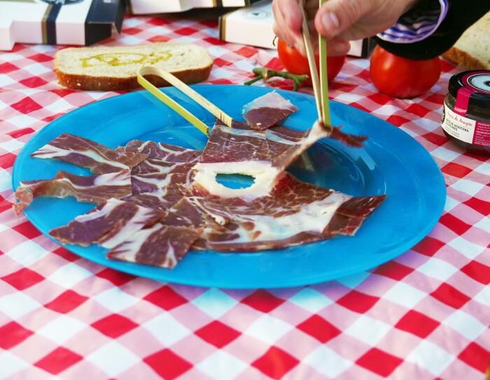 Primer plano de un plato jamón. El plato es azul y está sobre un mantel de cuadros rojos y blancos. Una mano con unas pinzas de bambú está cogiendo un corte.