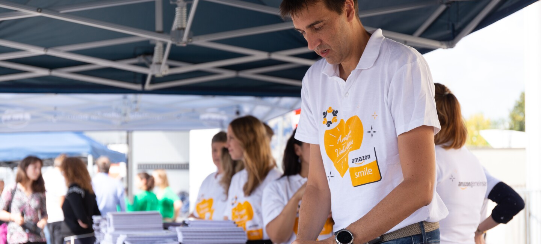Amazon Mitarbeiter helfen beim Verteilen von Schulmaterial, wie Bücher, Hefte, Mappen. Alle tragen das AmazonSmile T-Shirt mit einem orangenen Herz auf der Vorderseite.