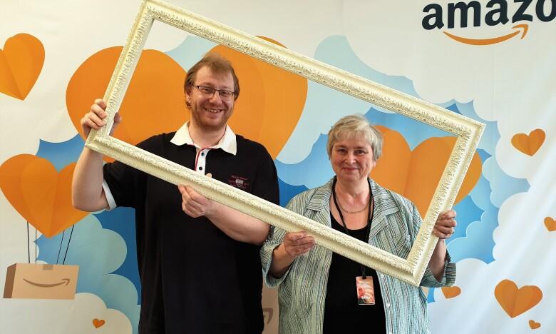 Ein Mann mit Brille steht neben seiner Mutter, einer älteren Dame, vor einer Fotoleinwand